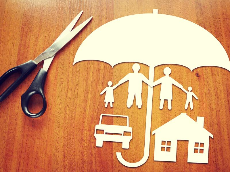 Formes de parapluie, d'une famille, d'une auto et d'une petite maison découpée dans du papier, un ciseau est posé à côté.