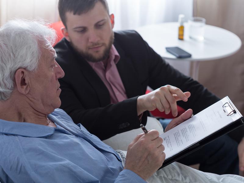 Homme âgé avec un document dans les mains, un homme plus jeune à côté lui dit quoi faire.