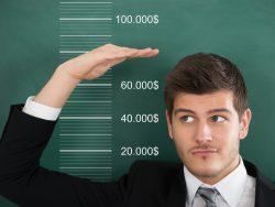 Un homme d'affaire à côté d'un tableau où il y a un salaire.