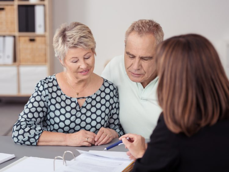 couple de retraités parlant avec une femme, des papiers sont posés devant eux.