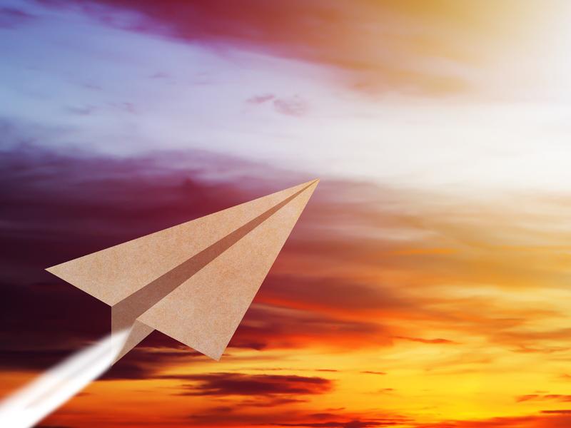 Un avion en papier dans un ciel de soleil couchant.