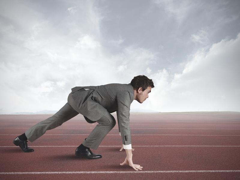 Un homme d'affaire en position pour se lancer dans une course.