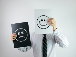 Un homme d'affaire tenant devant son visage un papier avec un smiley qui sourit. Dans son autre main, il a une feuille noire avec un smiley pas content.