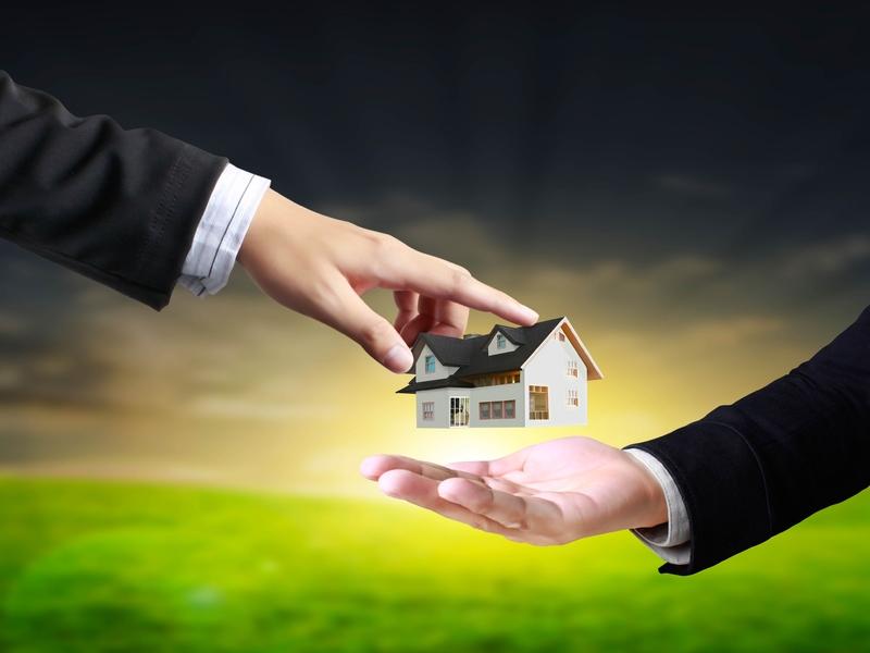 Un homme d'affaire donnant une petite maison à un autre homme d'affaire