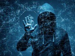 Un homme cagoulé qui a l'air très suspect. Il a une main posée sur un écran transparent sur lequel apparaît des signes informatiques.
