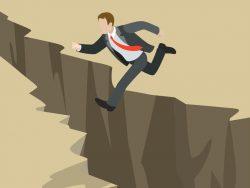 Un homme d'affaire sautant par dessus un gouffre.