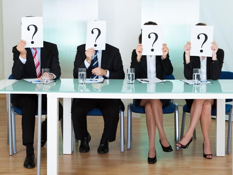 Des hommes et femmes d'affaire assis à une table tenant une feuille avec un point d'interrogation devant le visage.
