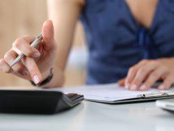 Une femme à une table avec une calculette, calculant les impôts.