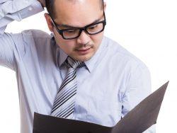 Un homme d'affaire qui se gratte la tête surpris, un dossier entre les mains.
