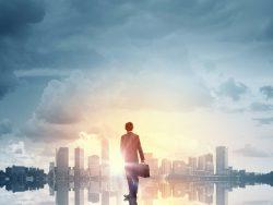 Un homme d'affaire marchant vers l'horizon où se dessine une ville.