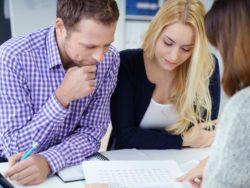 Un couple devant une table regardant une feuille qu'une conseillère leur explique.