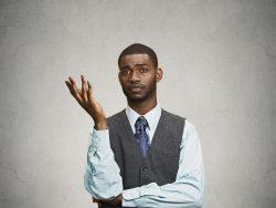 Un homme d'affaire levant une main en signe d'indifférence.