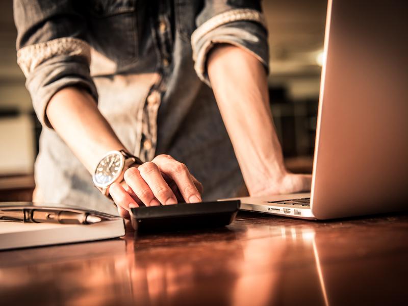 Un homme debout devant une table où sont posés un ordinateur et une calculette.