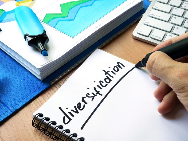 Une main qui écrit diversification sur un cahier