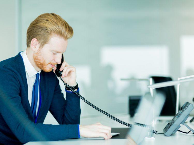 Un homme d'affaire assis à un bureau devant un écran. Il a un téléphone dans une main.