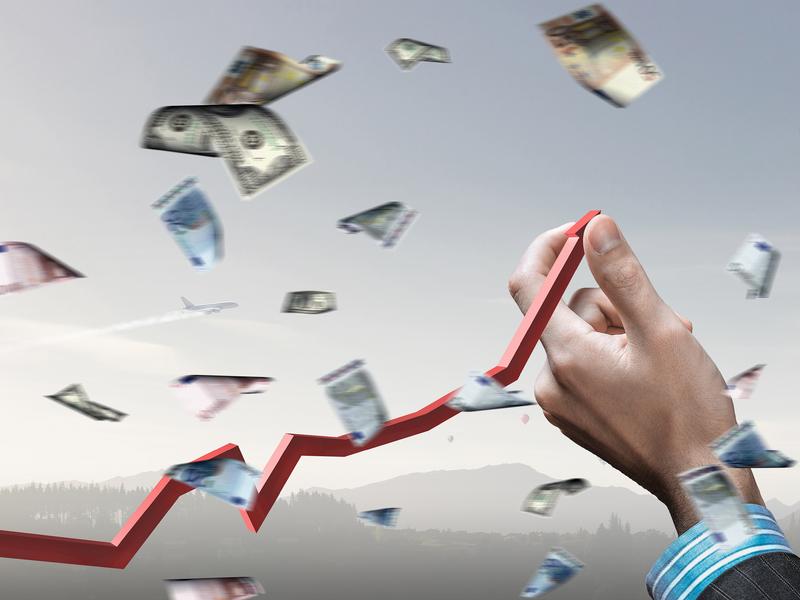 Un homme d'affaire redressant une courbe. Des billets de banque tombent tout autour.