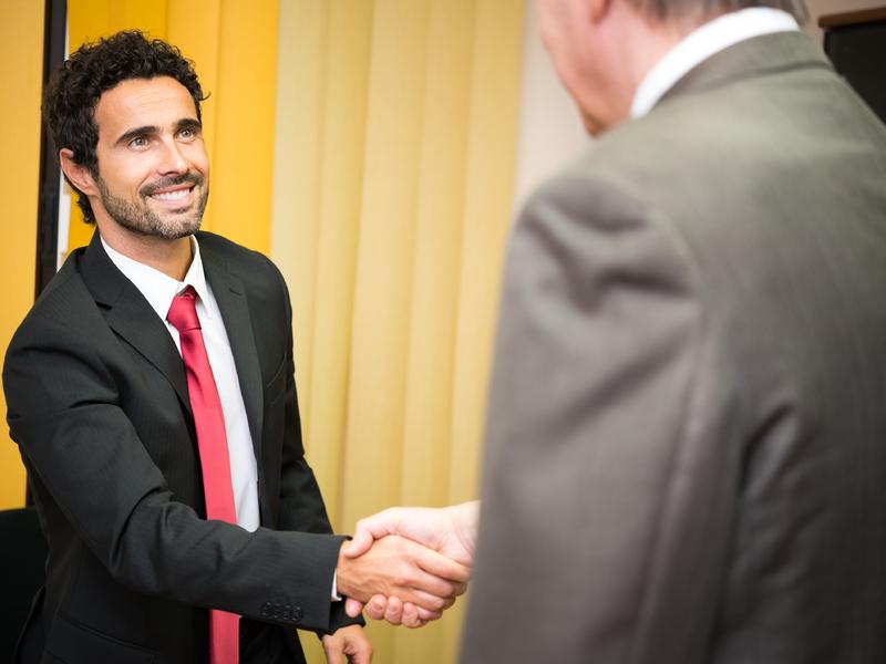 Un homme d'affaire souriant serrant la main à un autre homme d'affaire.
