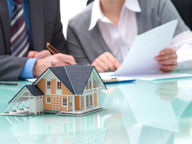 Une maquette de maison sur une table derrière laquelle on voit un homme et une femme d'affaire regarder une feuille.