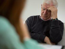 Vieux monsieur qui a l'air désespéré face à une jeune femme à une table