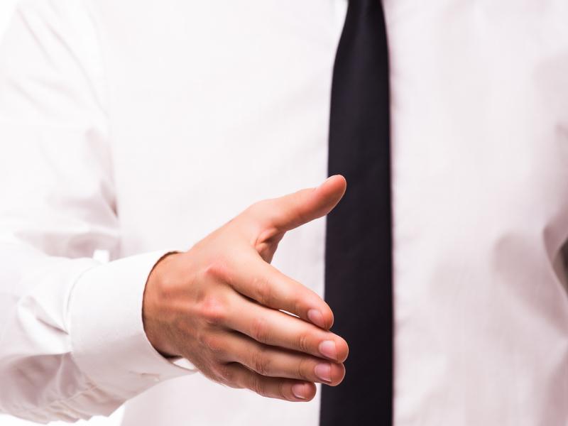 Un homme d'affaire tendant son bras pour une poignée de main