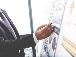 Un homme d'affaires qui réfléchit devant un tableau représentant des graphiques financiers.