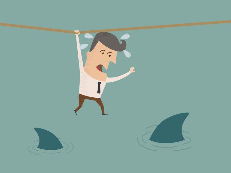 Un homme d'affaire qui se tient d'une main à une corde suspendue au-dessus de l'eau. On voit également deux ailerons de requin dans l'eau.
