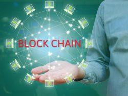 Un homme d'affaire tenant une sorte de roue composée d'ordinateurs reliés les uns aux autres. Le mot blockchain est inscrit au centre.