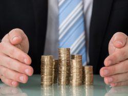 Le torse d'un homme d'affaire devant une table avec des petits tas de pièces posés devant lui.