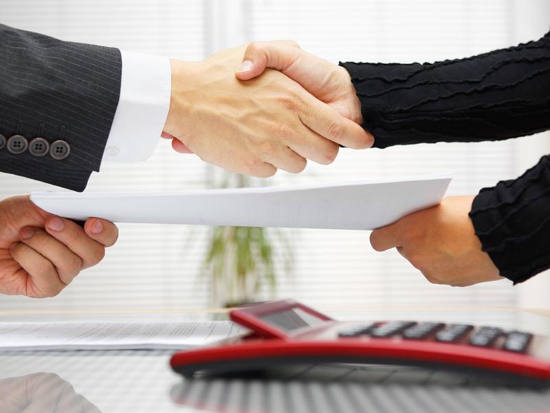 Deux hommes d'affaire se serrant la main et se donnant un document