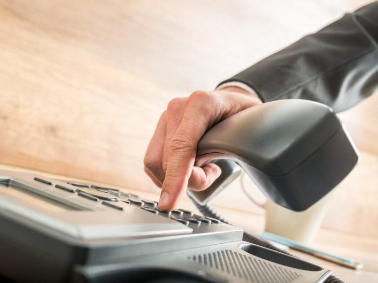 Un homme d'affaire tapant sur son clavier de téléphone pour passer un appel.