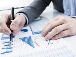 un homme d'affaire qui tient un stylo et regarde des tableaux de valeurs sur son bureau
