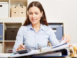Une femme d'affaire avec un classeur ouvert sur son bureau et une calculette.