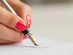 Une main de femme qui signe un document à la plume.