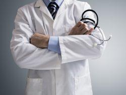 Homme les bras croisés portant une blouse de médecin, un stéthoscope dans la main.