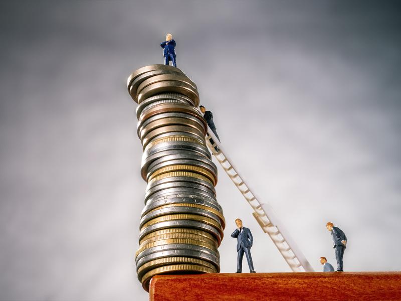 Une pile de sous au bord d'une table sur laquelle grimpe des hommes d'affaire qui ont posé une échelle contre.