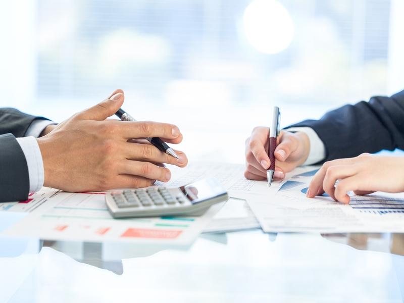 Deux hommes d'affaires écrivant sur des feuilles où on trouve des graphiques financier. Une calculette est posée devant l'un d'eux.