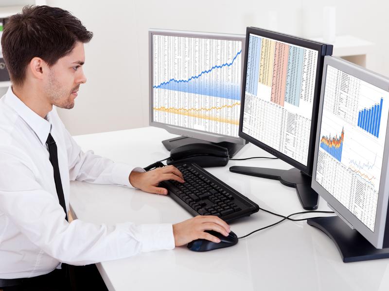 Un homme d'affaire assis devant trois écrans d'ordinateur