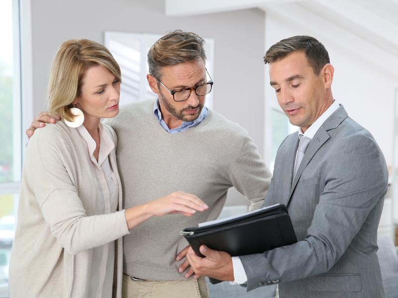 Un conseiller montrant un plan financier à un jeune couple.