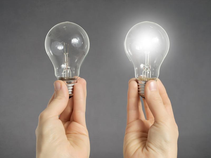 Deux mains, dans l'une il y a une ampoule éteinte, dans l'autre une ampoule allumée.