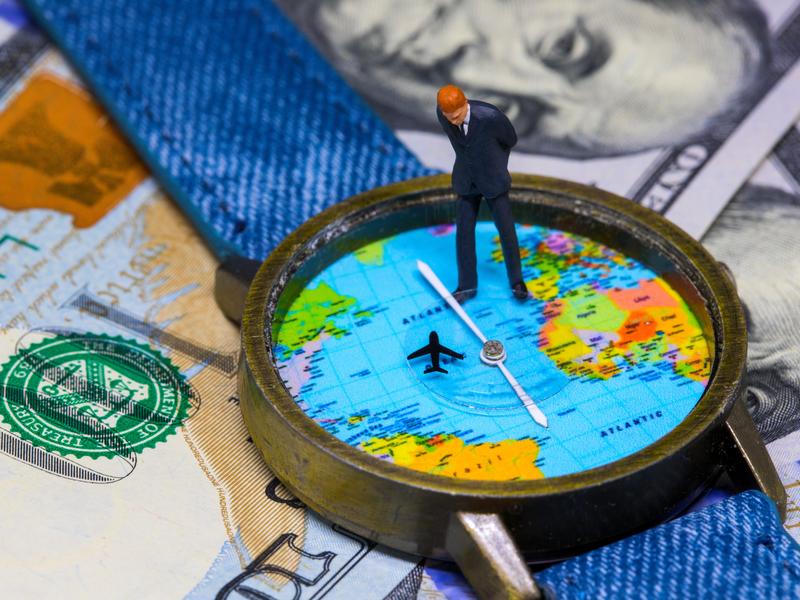 Un homme d'affaire placé sur une montre dans laquelle est représenté la carte du monde avec un petit avion.