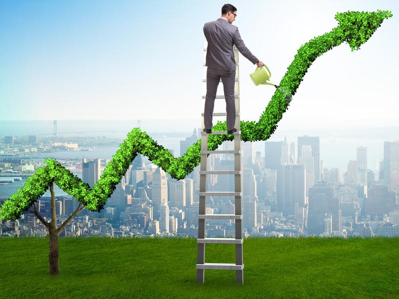 Un homme d'affaire arrosant une flèche verte de croissance.