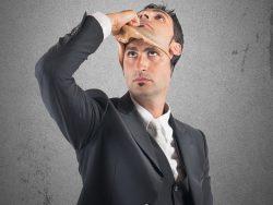 Un homme d'affaire qui enlève un masque sur sa tête pour montrer son visage.