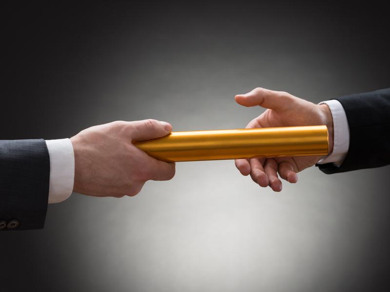 Une main d'homme d'affaires passant un témoin à une autre main d'homme d'affaires.