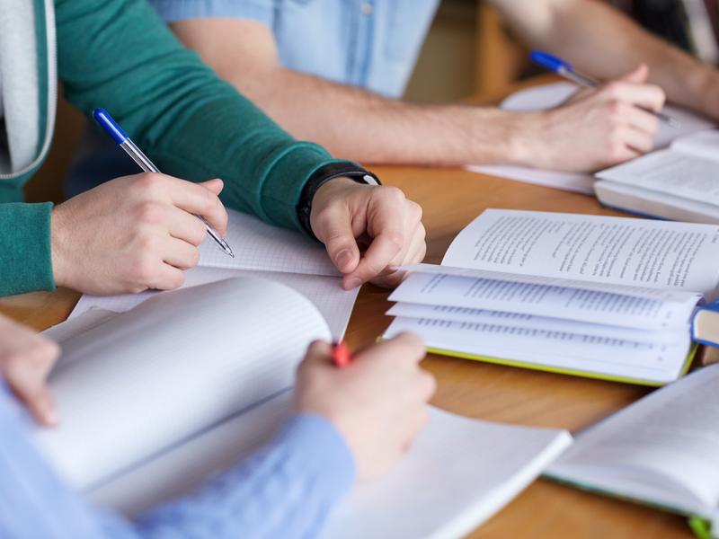 Trois jeunes personnes penchées sur des cahiers sur une table.