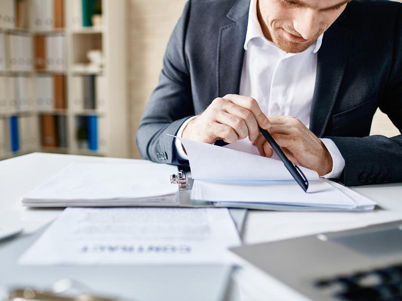 Un homme d'affaire assis à une table lisant des documents.