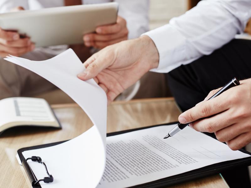 Un homme d'affaire regardant un texte de loi sur son bureau, un stylo à la main.