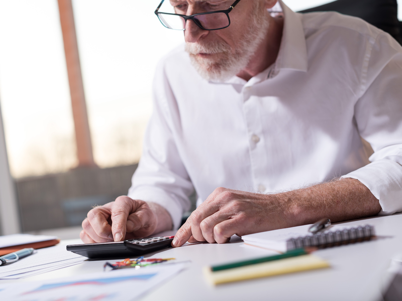 Un homme d'affaire avec une calculette à un bureau sur lequel sont posés des documents.