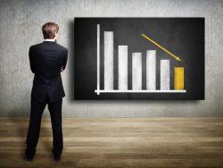 Homme d'affaire qui regarde un tableau où l'on voit une baisse des résultats.