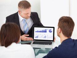 Un conseiller montrant un plan financier à un jeune couple de clients.