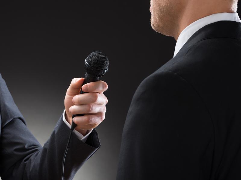 Un homme d'affaire tient un micro et interviewe un autre homme d'affaire